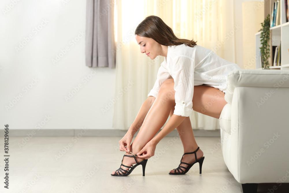 Fototapeta Beauty woman with longs legs putting high heels at home