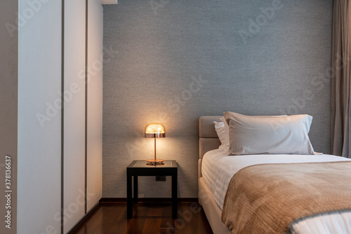 Stylish Bedroom corner with gray fabric headboard and bed with soft pillows setting with bed runner and gray wallcovering on the background / cozy interior design / modern interior