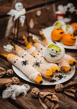 Sweet Table With Fruits And Treats For Halloween. Decorations Apple Bananas In The Form Of A Mummy With Eyes And Ghost. Spiders And Cockroaches
