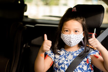 Smiling Asian Child Girl Thumbs Up For Good Drive Good Trip And Safe On The Road.Sitting And Buckle Up In The Car In The Seat For Children.Coronavirus Covid-19.Little Chinese Girl Wearing Mask In Car