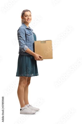 Obraz Full length shot of a young female carrying a cardboard box - fototapety do salonu