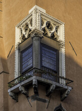 Vertical Shot Of A Beautiful Decorative Window With Flowers On The Ledge