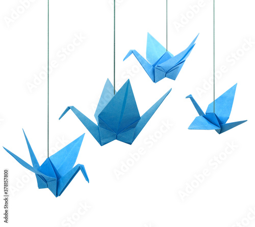 Photo Blue origami paper cranes haning isolated white