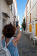 Woman taking photos with her smartphone in a pretty coastal village
