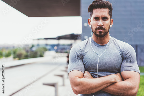 Handsome male runner dressed in active wear and electronic earphones concentrate Fototapet