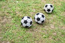 Three Soccer Balls In The Grass