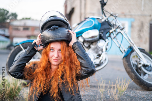 Fotografie, Obraz A red-haired woman puts on a helmet for safe motorcycle riding.