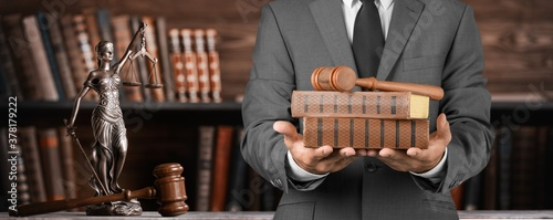 Fototapeta A lawyer with judge gavel and books in hands
