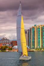 A Boat With Yellow Sail In Kingston Marina With Buildings On The Waterfront In The Background, Ontario, Canada