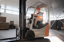 Delivery Concept. Driver At Warehouse In Forklift