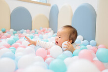 A Baby Playing With Balls