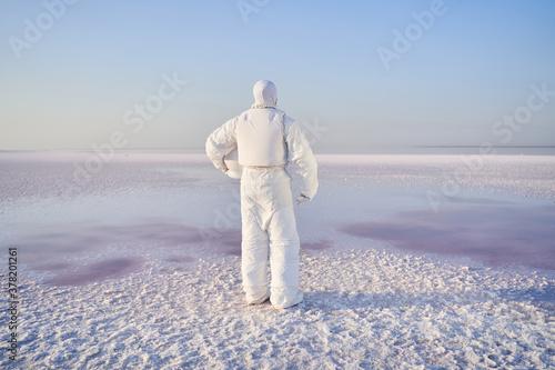 Astronaut standing with back on salty lake Fotobehang