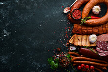 Set Of Sausage, Salami And Smoked Meat With Rosemary And Spices On A Black Stone Background. Top View. Free Space For Text.