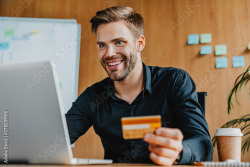 Young man holding credit card and doing online banking on laptop in office