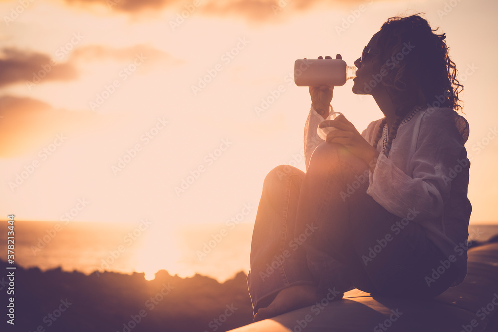 Fototapeta Happy and free woman alone enjoying the sunset on the coast with ocean view drinking a fresh drink - golden hour and vacation summer concept lifestyle for people