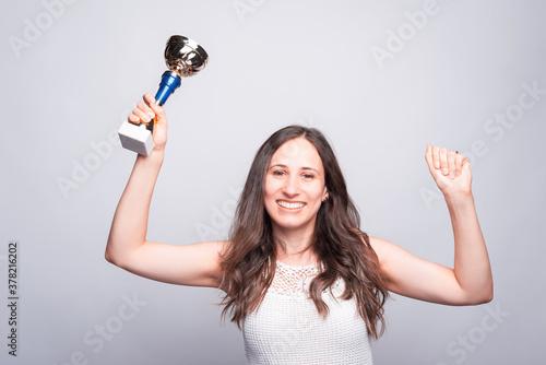 Fototapeta Cheerful young woman holding cup award, celebrating success obraz