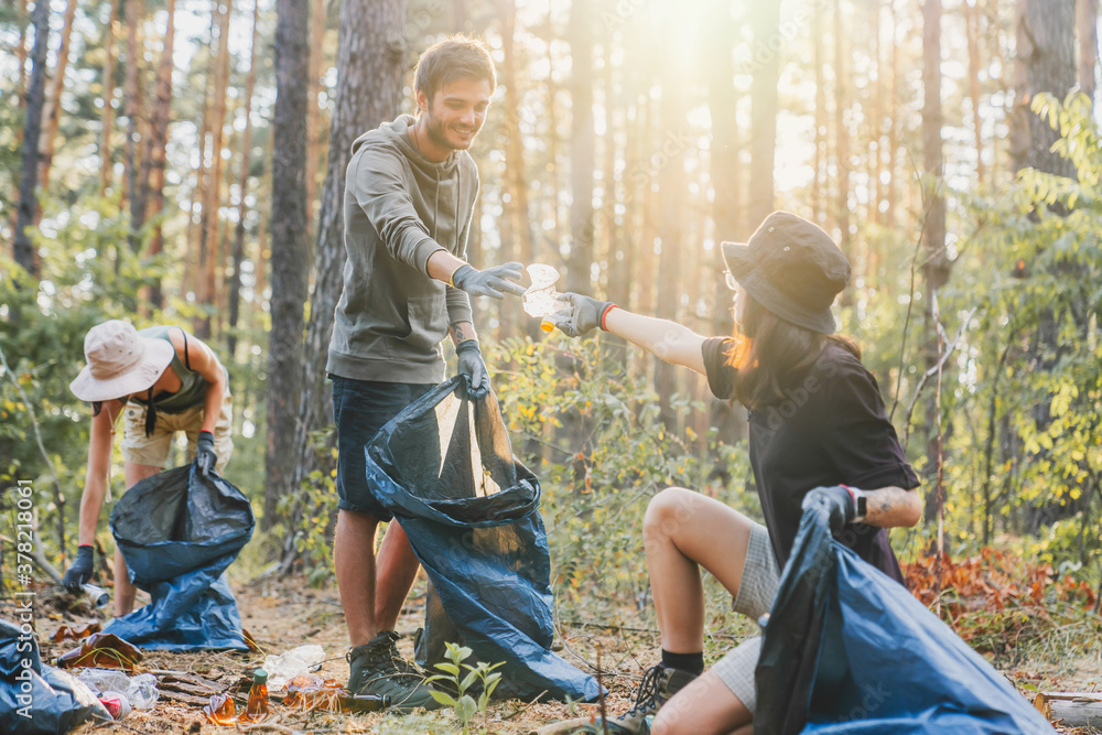 Fototapeta Boy and girl with friends picking up plastic trash from forest. Ecoway concept