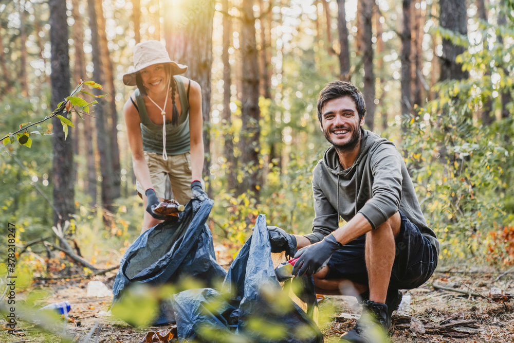 Fototapeta Portrait of young man and woman picking up trash from forest with look in camera