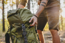 Close Up Of Male Hiker Holding His Camping Backpack. Traveler Opening Backpack While Traveling In Beautiful Wood
