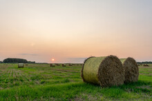 Nature Background. Two Bales Of Straw On Foreground On The Autumn Meadow During Wonderful Sunset Light
