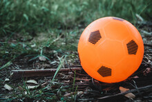 Closeup Shot Of An Orange Soccer Ball Toy Outdoors
