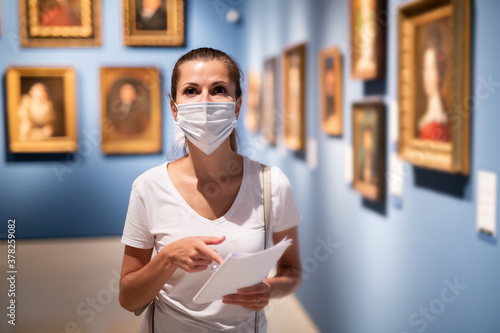 Focused adult girl in disposable face mask admiring paintings in museum holding Wallpaper Mural