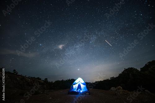 Fotografie, Obraz blue tent glows under a night sky full of stars.