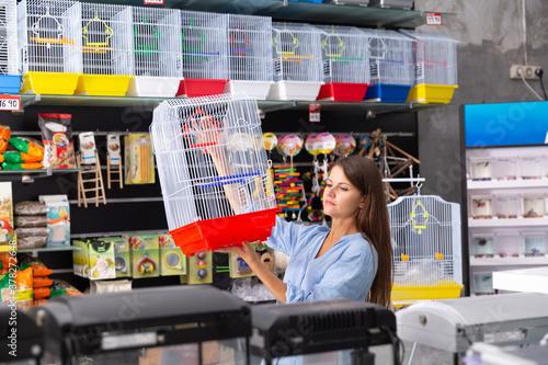 Obraz na plátně Portrait of young attractive brunette choosing birdcage in pet store