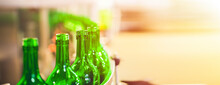 Beer Or Wine Bottles On The Conveyor Belt. Bottling Alkoholic Drink. Bottles Filled With Wine By An Industrial Machine In A Winery Factory.  Panorama