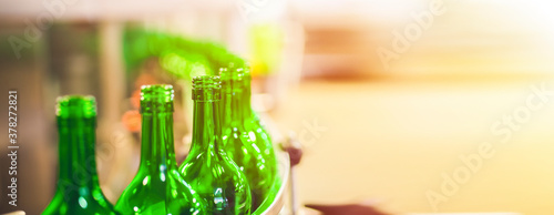 Fototapeta Beer or wine bottles on the conveyor belt. Bottling alkoholic drink. Bottles filled with wine by an industrial machine in a winery factory.  panorama obraz
