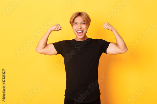 Fototapeta Portrait of happy and confident asian blond guy, flexing biceps, showing strong big muscles, standing yellow background obraz