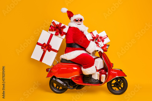 Fototapeta Full size profile side photo of white grey hair bearded santa claus ride motorbike deliver x-mas christmas gifts on noel night wear headwear isolated bright shine color background obraz