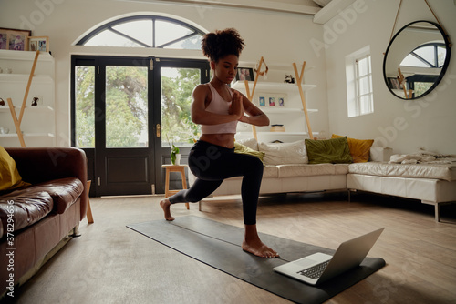 Healthy african woman watching video on laptop while exercising with hands joine Fototapeta