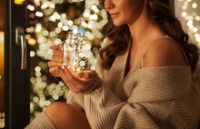 Christmas, Holiday And People Concept - Young Woman In Pullover Sitting At Window With Festive Garland Lights In Glass Mason Jar Mug At Home