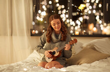 Christmas, Holiday And People Concept - Happy Young Woman Playing Ukulele Guitar In Bed At Home Bedroom At Night Over Festive Lights On Background