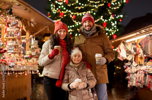 family, winter holidays and celebration concept - happy mother, father and little daughter with takeaway drinks at christmas market on town hall square in tallinn, estonia