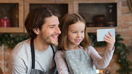 Adorable Little Girl Taking Selfie On Smartphone With Her Dad In Kitchen Canvas Print