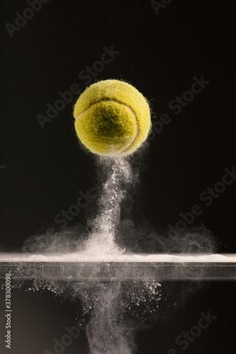 Pallina da tennis nella polvere bianca Fototapet
