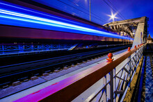 Blurry Streaks Of Light From A Speeding Train. The Train Passes Through The Arches Of The Railway Bridge At Night. Neon Light. Dynamic Pulsation Of Big City Life. High Quality Photo