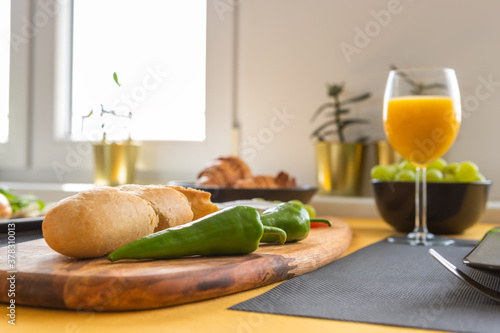 Breakfast in a modern, bright interior - fresh baguette sliced on a board, two jalapeno peppers, croissants, grape and orange juice in a glass