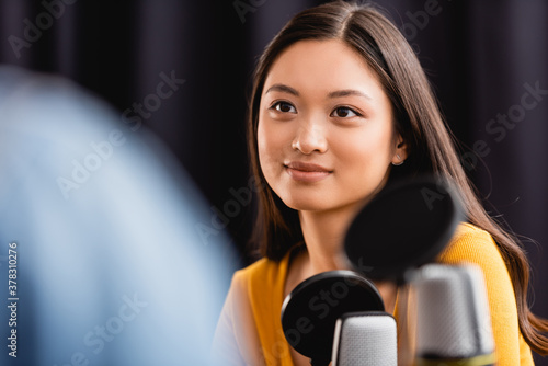 Fotografija selective focus of young, brunette asian broadcaster near microphone in radio st