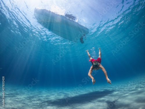 Man dives into the sea to reach the sandy bottom, dinghy boat at anchor in background Fototapet