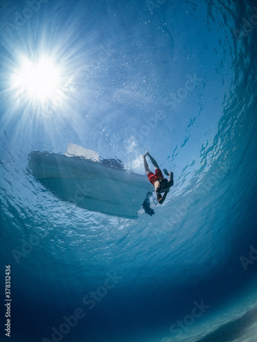 Man dives into the sea to reach the sandy bottom, dinghy boat at anchor in background Canvas Print