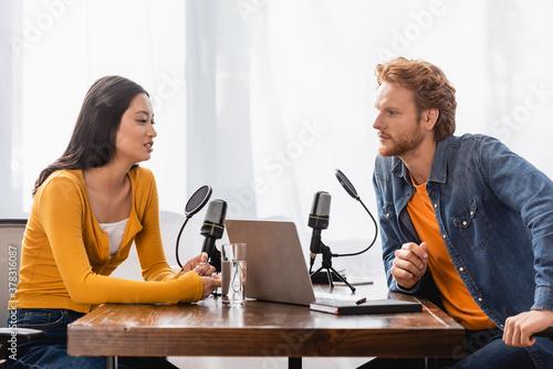 Fototapeta redhead radio host interviewing brunette asian woman near microphones and laptop in studio obraz
