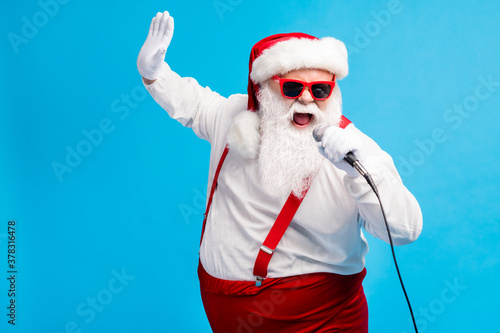 Photo of old man grey beard hold mic open mouth sing karaoke raise arm wear santa claus x-mas costume cap sunglass suspenders white shirt gloves isolated blue color background