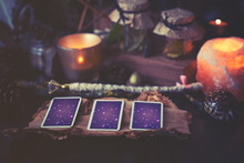3 Tarot Cards Spread Lying On A Black Table With Magic Items. Toned To Cold Colors In Shadows.