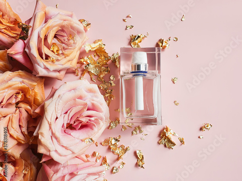 Fotografie, Obraz Perfume bottle, pink gold roses and pieces of golden paper on powdery pink background