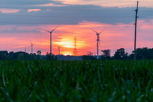 Wind Turbines / Wind Mills/ Wind Power With High Power Wires / Lines Partially Silhouetted By A Sun Rise / Sunset.  Flat Midwest Farm Fields For Foreground.