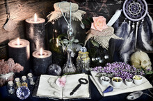 Still Life With Magic Bottles, Dreamcatcher, Jars With Plants And Herbs, Burning Black Candles And Crystal On Witch Table. Esoteric, Gothic And Occult Background, Halloween Mystic Concept.