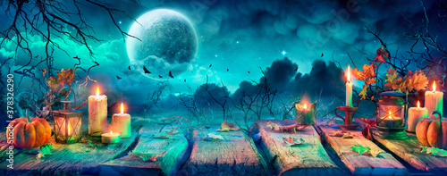 Fototapeta Spooky Halloween Table With Candles And Pumpkins At Night With Full Moon  obraz